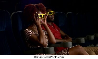 Happy African American couple watching movie 3D In theatre. Close up
