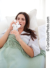 Sick woman blowing lying on the sofa