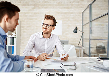 Consultation - Young businessman looking at co-worker during...