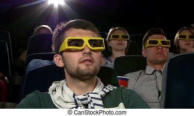 Young mans watching movie at cinema: thriller, Close up, 3D...