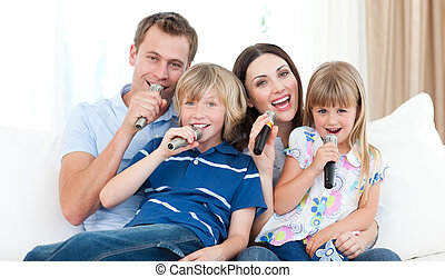 Happy family singing a karaoke together at home