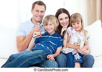 Smiling young family singing a karaoke together