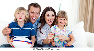 Smiling Young family watching TV on the sofa