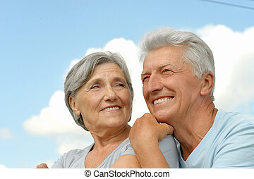 elderly couple posing against the sky