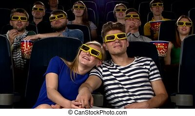 Couple in cinema watching a movie with 3D glasses Young...