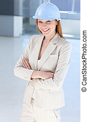 Attractive female architect wearing a hard hat with folded...