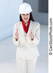 Beautiful female architect wearing a hard hat with thumbs up