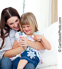 Cute girl sitting on her mother\'s lap celebrating a goal