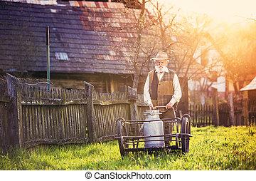 Farmer with milk kettle - Senior farmer carrying kettle full...
