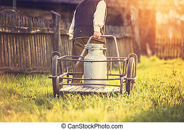 Farmer with milk kettle - Senior farmer carrying kettle full...