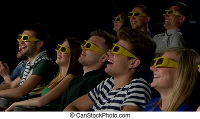 Young people watch movies in cinema: comedy in 3D. Close up...