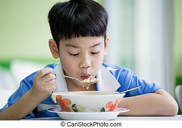Young Chinese Boy Sitting At Home Eating Meal - Young asian...
