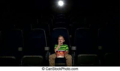 Smiling little boy watching movie in a cinema