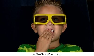 Smiling little boy watching movie in a cinema, 3D glasses, close up