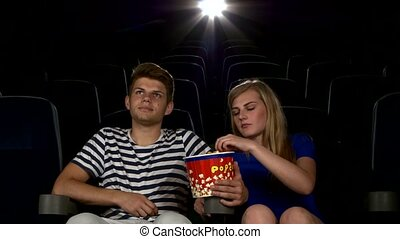 Great movie! Young couple feeding each other at the cinema -...