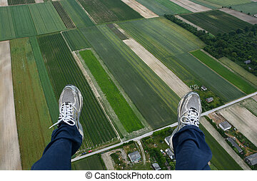 Man paragliding above  fields of crops