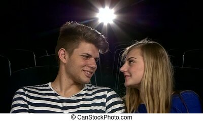 Stylish couple having romatic moment in a movie theater.  Close up