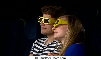 Couple in cinema watching a movie with 3D glasses. Close Up...