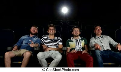 company of the men watching a movie at cinema. smiling,...