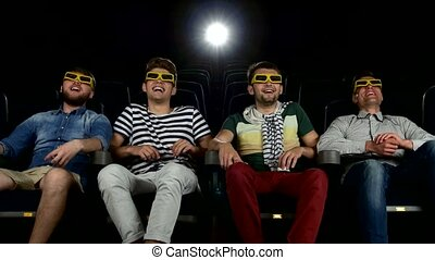 company of the men watching a movie at cinema smiling,...