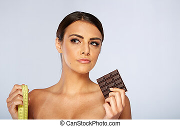 portrait of a brunette young woman with chocolate and tape...