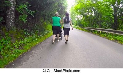 Two woman pushing baby stroller in a rural road, rear view