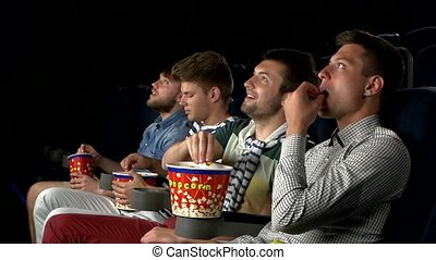 Young people watching movie in cinema eating popcorn and...