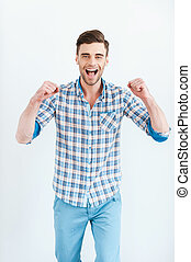 Joy has no limits. Happy young man in shirt gesturing and...