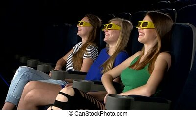 Young friends watching a film at the cinema, 3d glasses,...