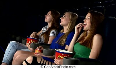 girl watching medy film at the cinema, eating popcorn -...