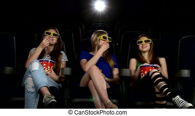 company of girl watching a movie at cinema smiling, talking...