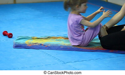 Girl in spotzale perform exercises - Little girl in the gym...