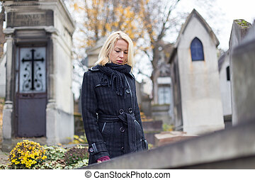 Solitary woman visiting relatives grave - Solitary woman...