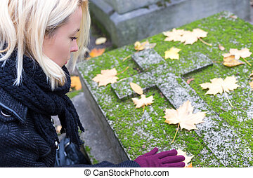 Solitary woman visiting relatives grave. - Solitary woman...