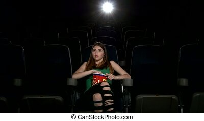 young girl in horror film 3D at the cinema. eating popcorn