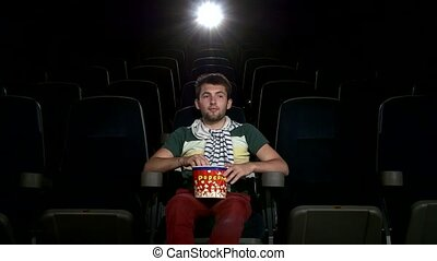 happy young man watching movie alone in empty theater -...