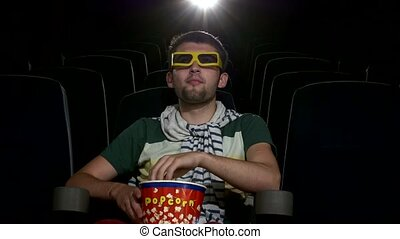 happy young man watching movie alone in empty theater,...