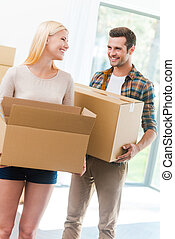 Happy to start a new life together. Happy young couple holding a cardboard box and looking at each other while other carton boxes laying on background