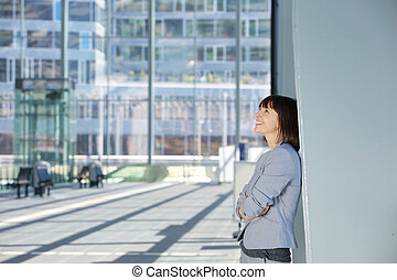 Happy business woman standing alone - Side portrait of a...