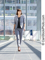Attractive professional business woman walking - Full body...