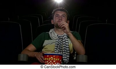 young man watching movie alone in empty theater, close up -...