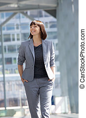 Smiling business woman walking - Portrait of a smiling...