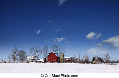 Winter landscape - Red barn in the middle of snow during...