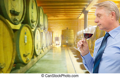 senior man smelling red wine in cellar - people, winery,...