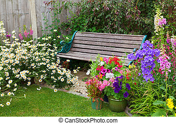 Cottage garden with bench and containers full of flowers -...