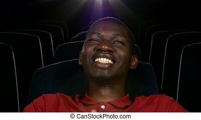 Happy African American watching movie In theatre