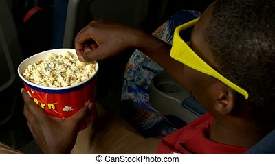 African American man with a bucket of popcorn is sitting in a cinema