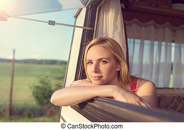 Beautiful woman sitting in a camper van - Beautiful young...
