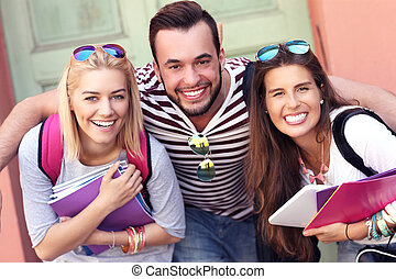 Group of happy students studying outdoors - A picture of a...