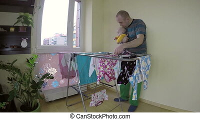 father with baby laundry - Father man with newborn baby on...